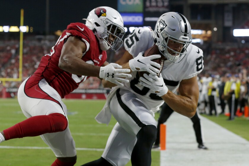 Oakland Raiders tight end Derek Carrier (85) scores a touchdown as Arizona Cardinals defensive back Rudy Ford defends during the first half on Thursday in Glendale, Ariz.