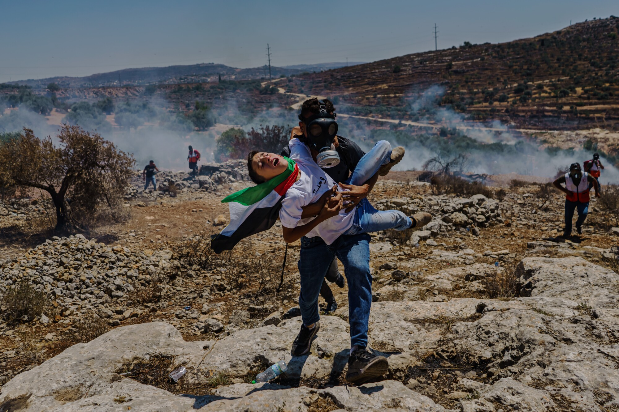 A Palestinian struggling to breathe is carried away during a protest