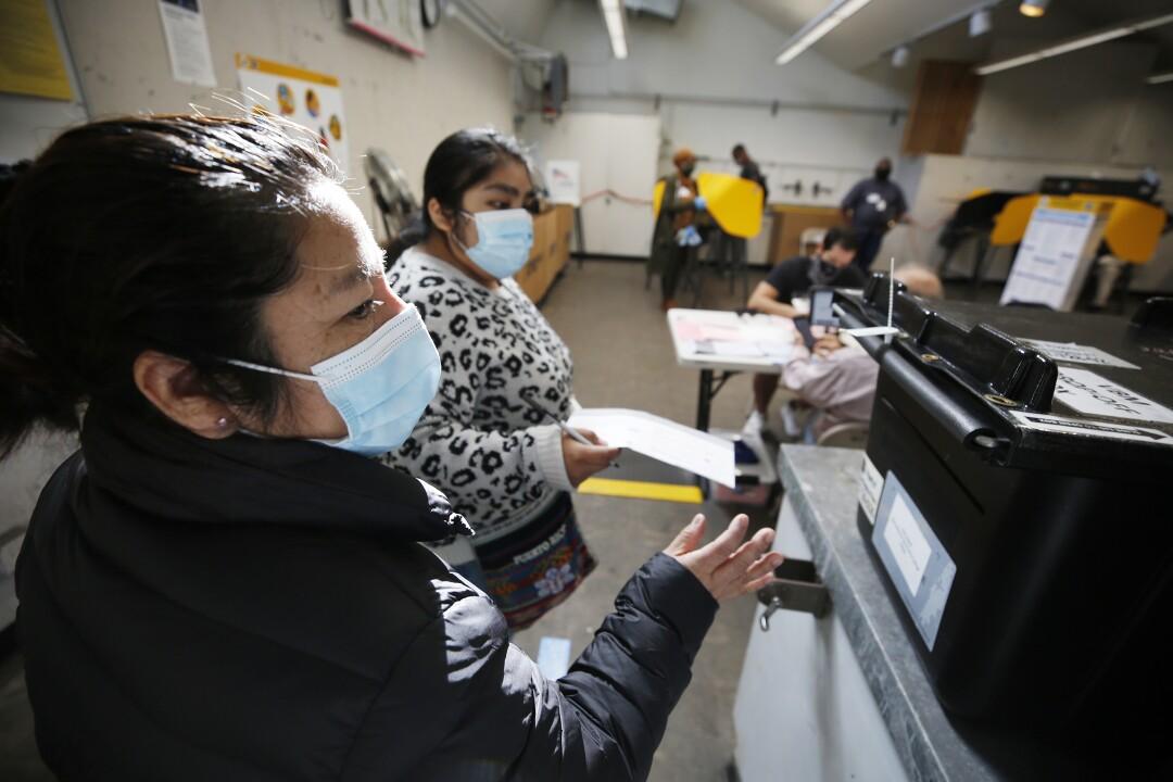 Francisca Marques, links, mit Tochter Julia Marques, geben ihre Stimmzettel in den Briefkasten