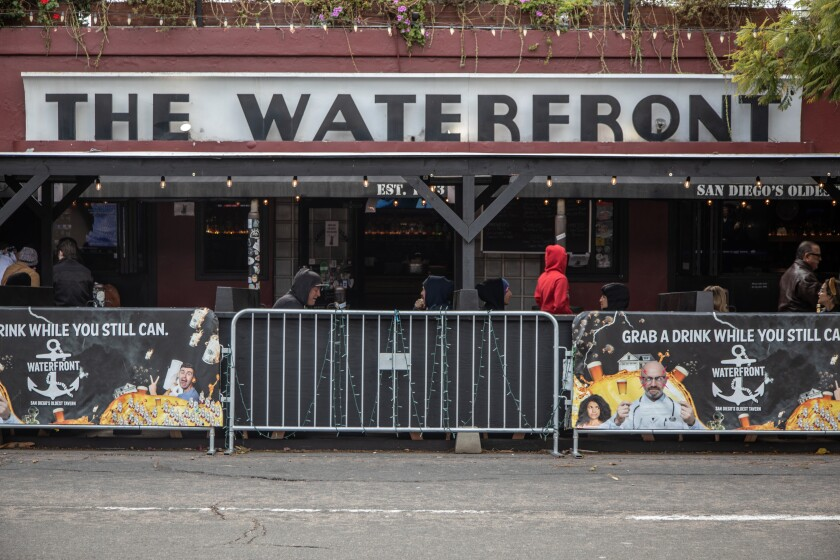 Diners at tables in front of Little Italy's The Waterfront Bar and Grill are separated from the street by metal barriers.