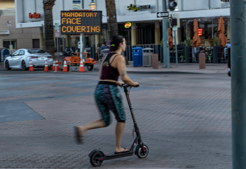 A woman on a scooter ignores the mandatory mask order in downtown Palm Springs in Riverside County.
