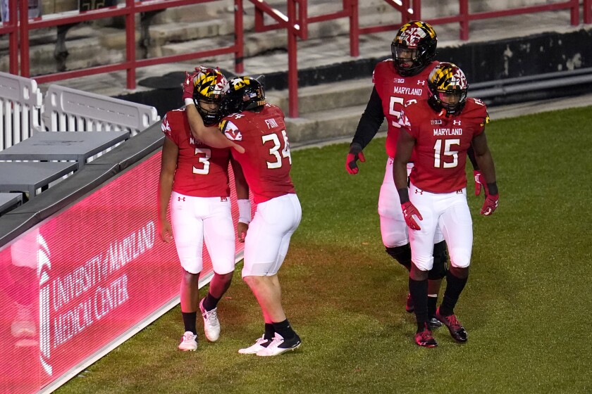 Maryland's Taulia Tagovailoa (3) is congratulated by Jake Funk (34) after scoring an overtime touchdown against Minnesota.