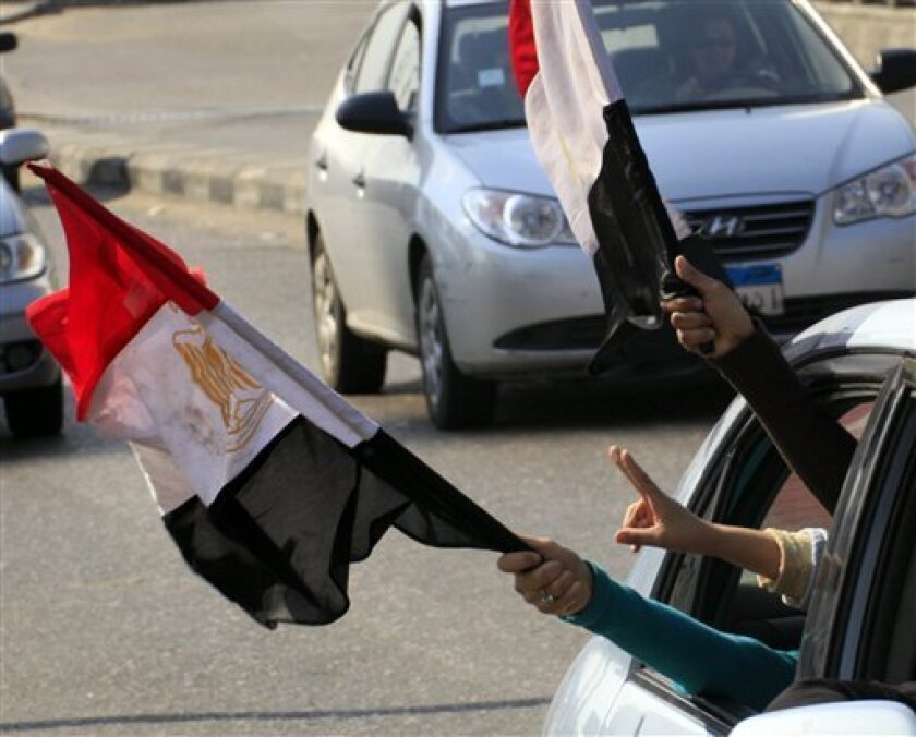 Anti-government protesters peer out of their vehicle as they flash V signs and wave by Egyptian flags in Cairo street, Egypt, Friday, Feb. 11, 2011. Egypt's military threw its weight Friday behind President Hosni Mubarak's plan to stay in office through September elections while protesters fanned o