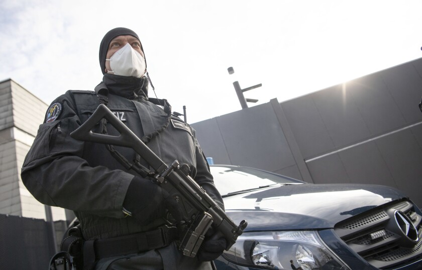 """An armed court officer stands in front of an entrance to the grounds of the Higher Regional Court in Stuttgart-Stammheim, Germany, Tuesday, April 13, 2021. Twelve suspected members and supporters of the right-wing terrorist group """"Gruppe S."""" must answer to the Stuttgart Higher Regional Court in a state protection trial. (Photo/AP via Pool)"""