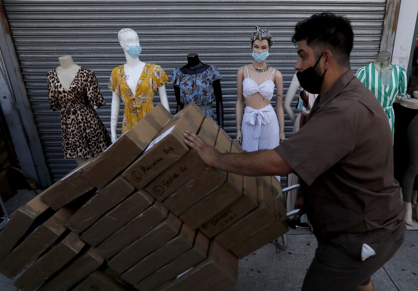 A masked deliveryman moves packages past mannequins wearing similar facial coverings in the garment district in downtown L.A.