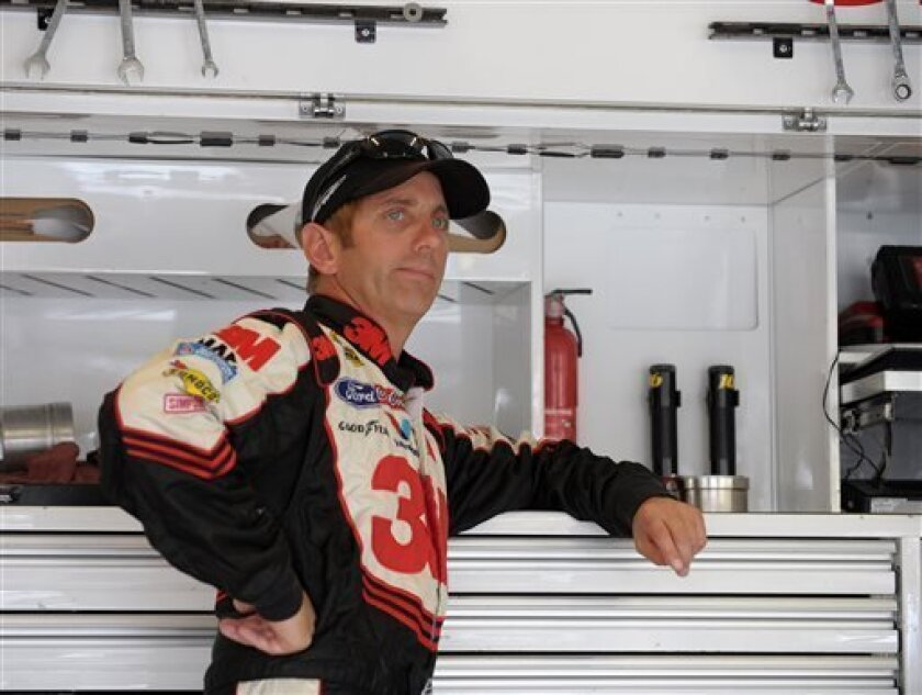 Driver Greg Biffle leans on a toolbox in the garage area before beginning practice for Sunday's NASCAR Sprint Cup Series auto race at Atlanta Motor Speedway, Saturday, Aug. 31, 2013 in Hampton, Ga. (AP Photo/David Tulis)
