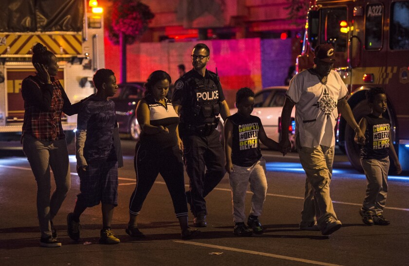 Police escort civilians away from the scene of a shooting on Sunday in Toronto.