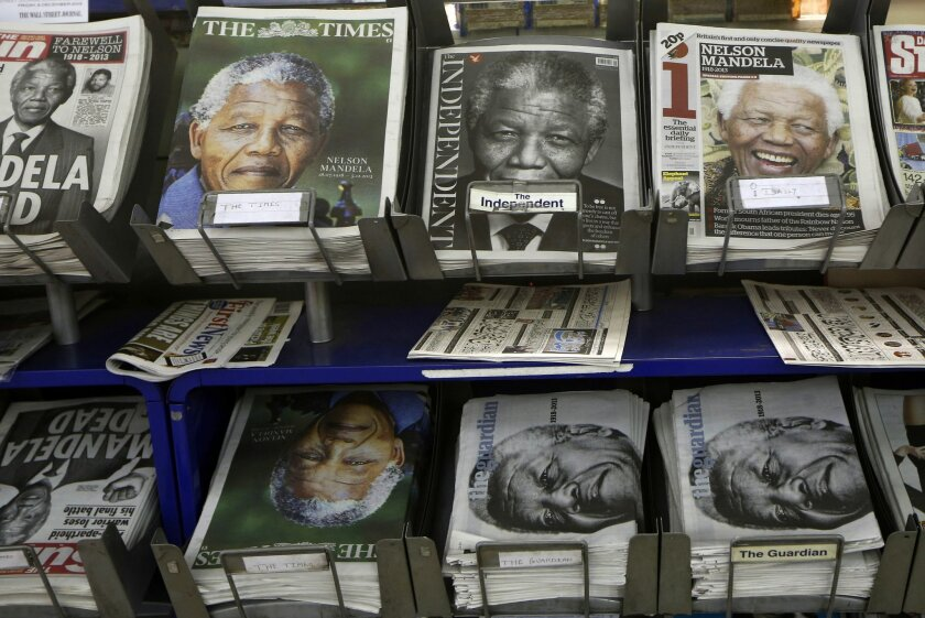 Newspapers with pictures of Nelson Mandela on the front page are on sale at a newsagent in London, Friday, Dec. 6, 2013. Mandela passed away Thursday night after a long illness. He was 95. As word of Mandela's death spread, current and former presidents, athletes and entertainers, and people around the world spoke about the life and legacy of the former South African leader. (AP Photo/Sang Tan)