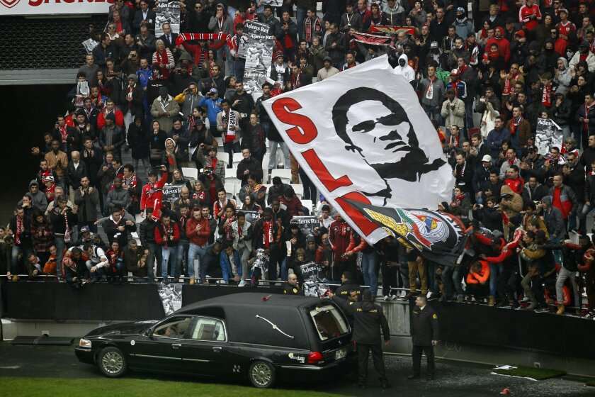 """The remains of the Portuguese soccer player legend Eusebio are carried inside a car as supporters cheer during his memorial tribute at the Benfica's Luz stadium in Lisbon, Monday, Jan. 6, 2014. Eusebio, the Portuguese football star who was born into poverty in Africa but became an international sporting icon and was voted one of the 10 best players of all time, has died aged 71, his longtime club Benfica said. Few supporters hold posters with the photograph of Esusebio that read in Portuguese: """"Bye King"""". (AP Photo/Francisco Seco)"""