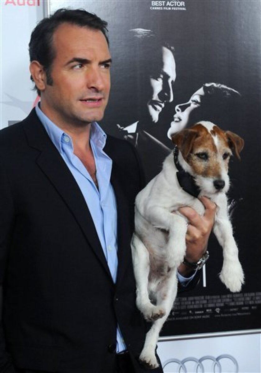 """FILE - In this Nov. 8, 2011 file photo, Jean Dujardin holds his co-star Uggie the dog arrive at the AFI gala screening of """"The Artist"""" at Grauman's Chinese Theater in Los Angeles. Hollywood really has gone to the dogs this year. There's even a brand-new awards show, The Golden Collar Awards, honoring canine performers. Alan Siskind, creator of Dog News Daily, a website and marketing firm, came up with the idea to honor on-screen dogs in January when he noticed how many films prominently featured man's best friend.(AP Photo/Katy Winn, file)"""