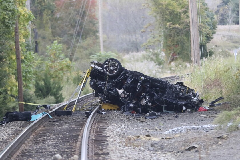 The remains of a Porsche SUV that plummeted off an overpass, rests on train tracks below, where it burst into flames Sunday afternoon, killing two teenagers and sending a third to a hospital with serious injuries. in Pearl River, NY, Sunday, October 13, 2019. (Photo by Kevin Wexler/NorthJersey.com via AP)