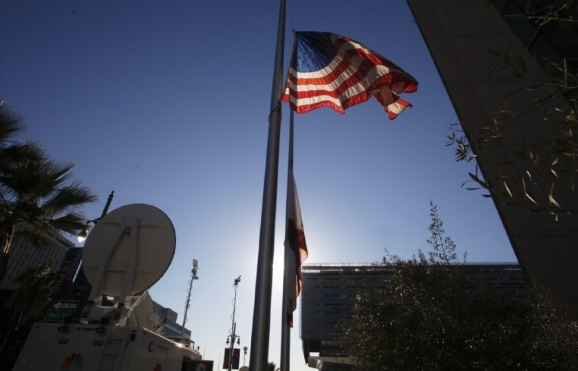 The flag in front of LAPD headquarters flies at half-staff for law enforcement officers believed to have been killed by former LAPD officer Chris Dorner.