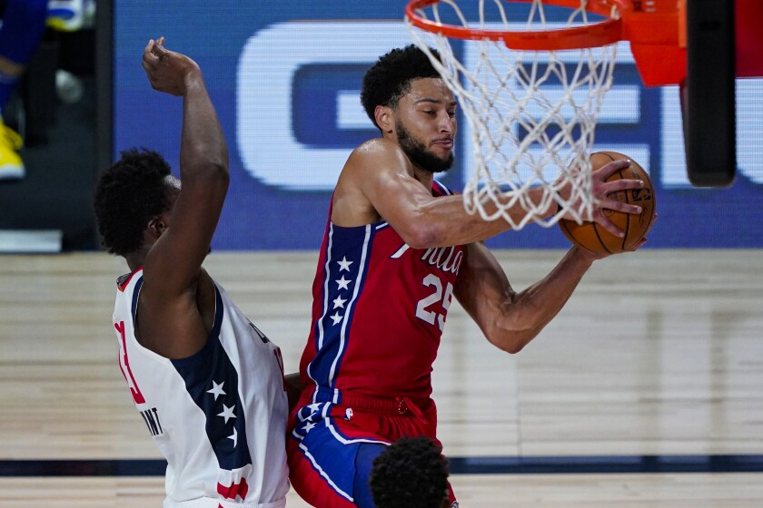 Philadelphia 76ers guard Ben Simmons (25) grabs a rebound in front of Washington Wizards center Thomas Bryant (13) during the second half of an NBA basketball game Wednesday, Aug. 5, 2020 in Lake Buena Vista, Fla. (AP Photo/Ashley Landis)
