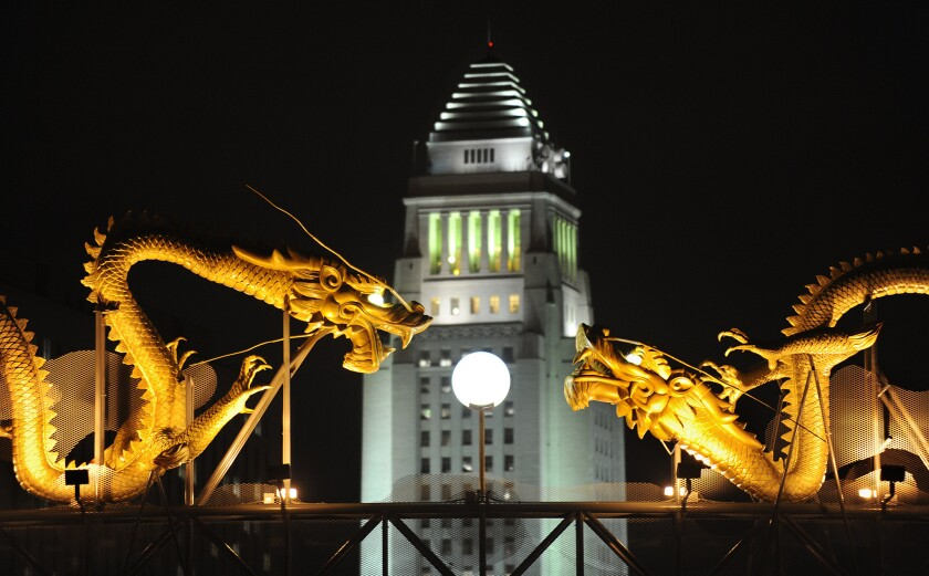 Los Angeles City Hall stands in between statues of dragons in Chinatown.