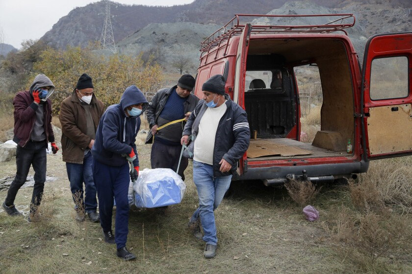 Ethnic Armenians carry a coffin with the body of their relative Sergei Gabrilyan, moved from a grave, to repatriate his remains to Armenia, in Kalbajar in separatist region of Nagorno-Karabakh, Monday, Nov. 16, 2020. It is unclear when any civilians might try to settle in Karvachar, which will now be known by its Azeri name Kalbajar, or elsewhere. Armenians who are going to leave separatist region of Nagorno-Karabakh dig up the remains of their ancestors to bring them from the territory, which is to be handed over to Azerbaijanis. (AP Photo/Sergei Grits)