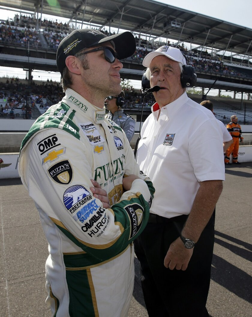 Ed Carpenter, left, and Roger Penske watch as cars run during qualifications for the Indianapolis 500 auto race at Indianapolis Motor Speedway in Indianapolis, Sunday, May 22, 2016. (AP Photo/Darron Cummings)