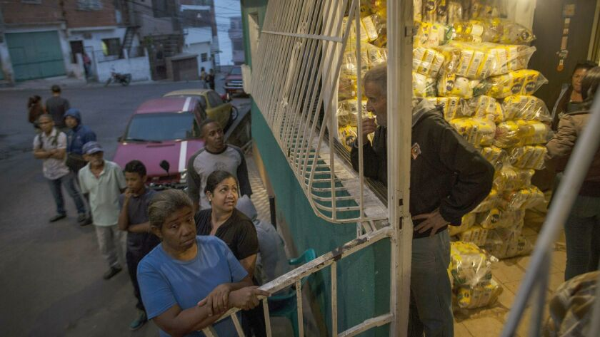 "Neighbors wait to receive bags of subsidized food distributed under a government program named ""CLAP"
