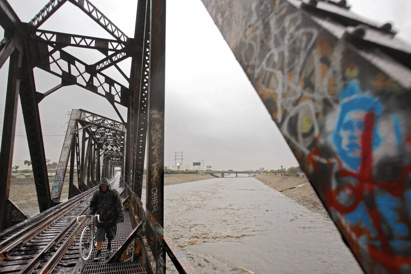 A man walks along an old Union Pacific Bridge as the Los Angeles River flows in South Gate.