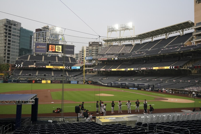 San Francisco players stand near the dugout as the team's game against the San Diego is postponed Friday, Sept. 11, 2020.