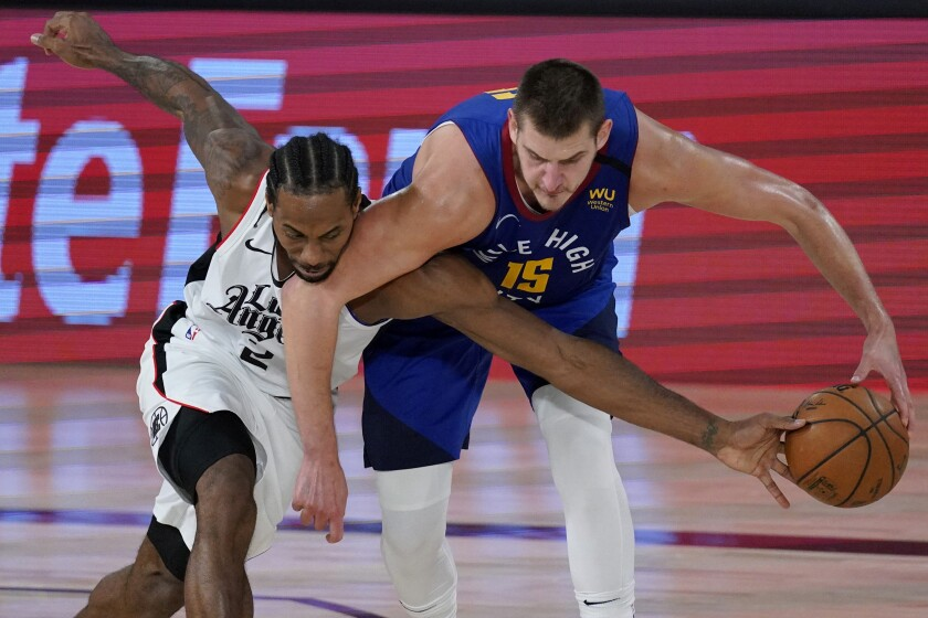 Clippers forward Kawhi Leonard tries to steal the ball from Nuggets center Nikola Jokic during Game 5 on Sept. 11, 2020.