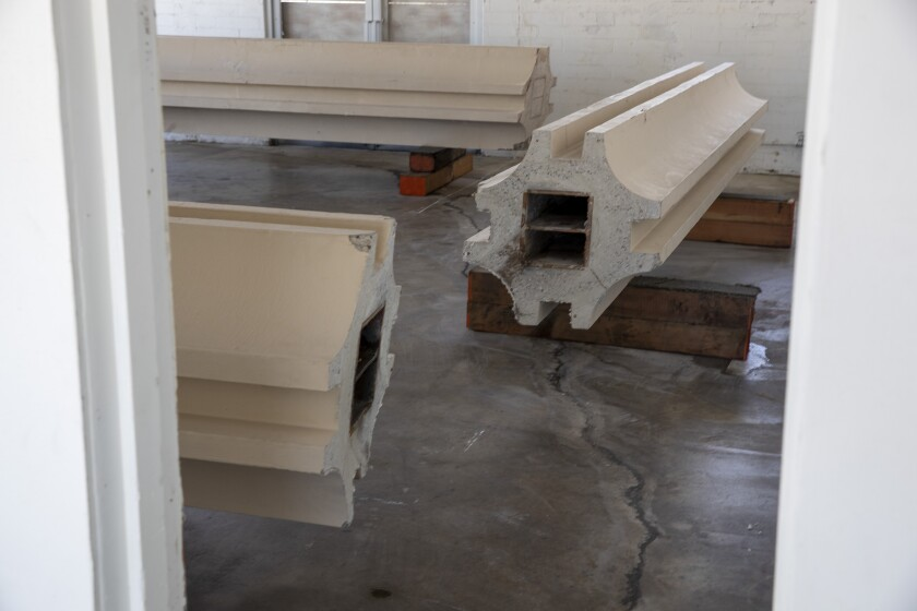 Fragments of columns from LACMA's Ahmanson building are shown resting on their side in a storefront gallery space.