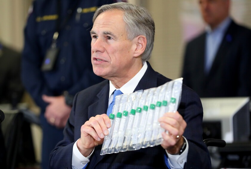 Texas Gov. Greg Abbott holds COVID-19 test collection vials.