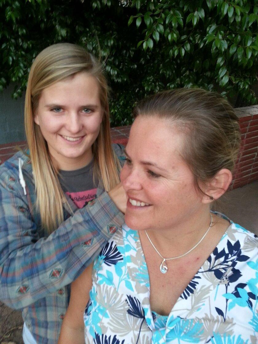 Kristen Rosier puts her winning necklace on her mom, Anna Rosier.