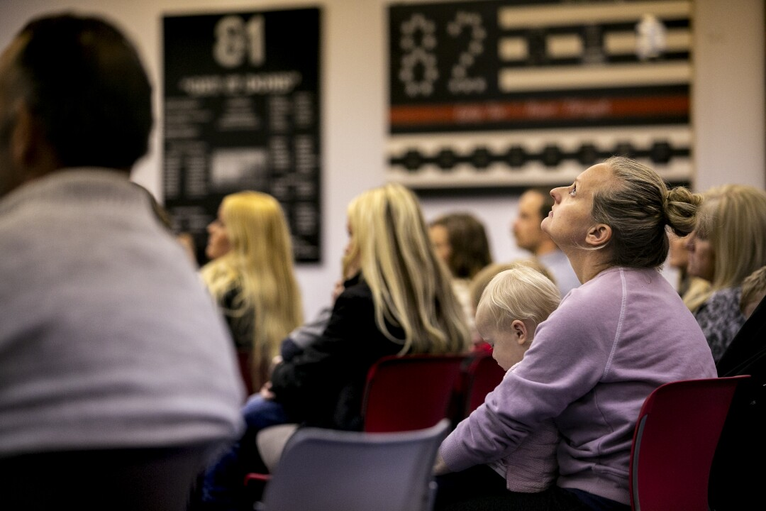 Recruit Colby Jackson's wife Becky Jackson clutches her toddler Stella as academy brass talk about the rigors of the academy and the strain on families on orientation day for the 87th academy.