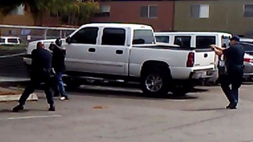 In this frame from video provided by the El Cajon Police Department, a man, second from left, faces police officers in El Cajon, Calif. The man reportedly acting erratically at a strip mall in El Cajon was shot and killed by police after pulling an object from his pocket.