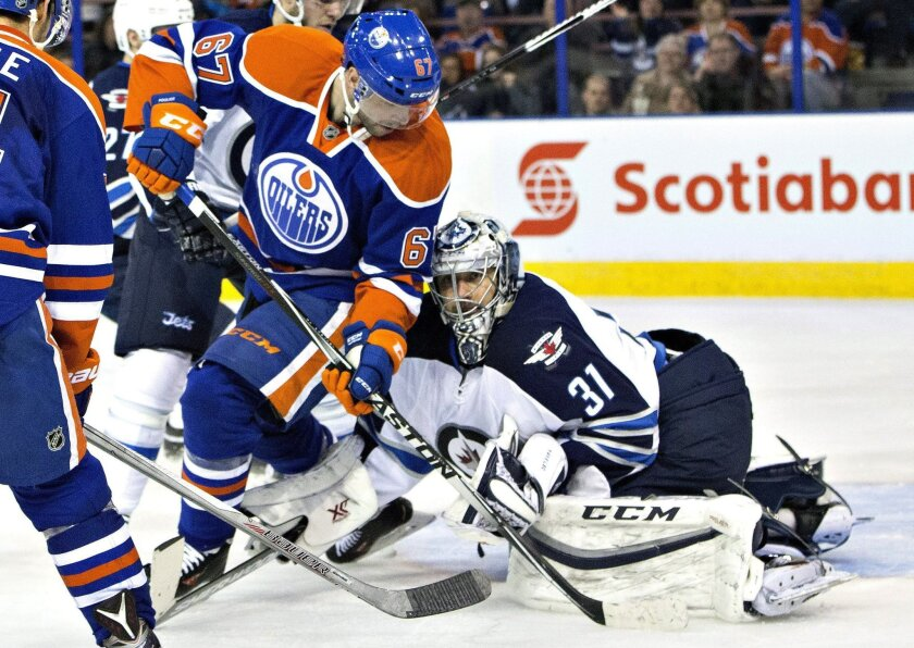 Winnipeg Jets goalie Ondrej Pavelec (31) is screened by Edmonton Oilers' Benoit Pouliot (67) during the second period of an NHL hockey game Saturday, Feb. 13, 2016, in Edmonton, Alberta. (Jason Franson/The Canadian Press via AP)