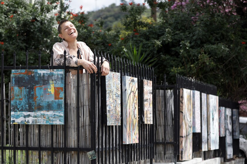 Olivia Arthur, a sound mixer who started painting three years ago, hangs her work outside her Highland Park home and  on a fence on the other side of the street.