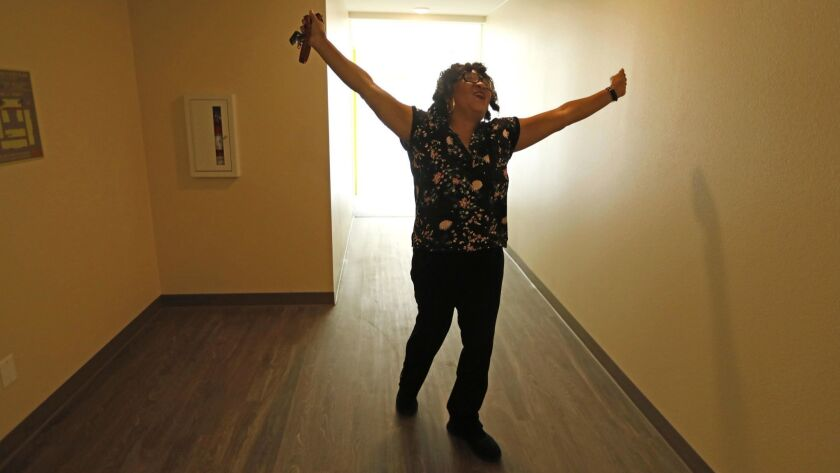 LOS ANGELES, CA - AUGUST 9, 2018 - Carla McCue, 62, raises victorious arms after moving into her new