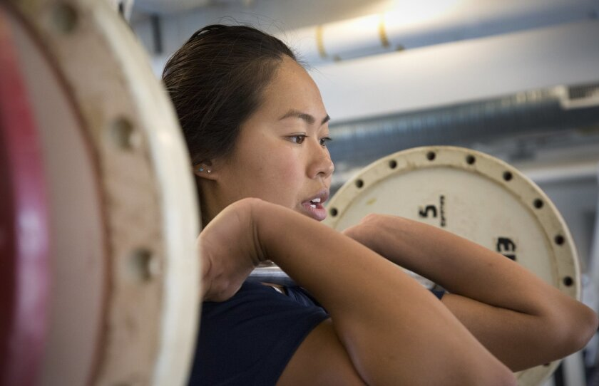 "UCSD swimmer Sandy Hon, 21, works out with weights as part of her training. The Navy SEAL physical screening test looks ""definitely doable"" to her."