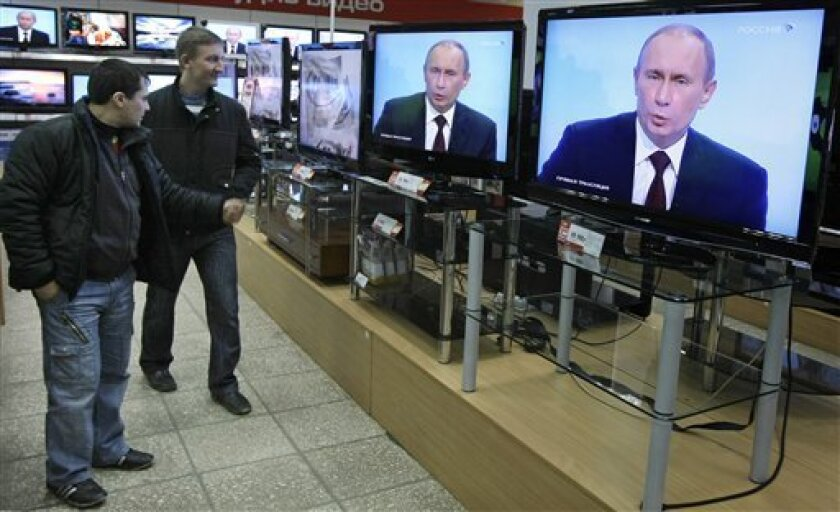 Russian President Vladimir Putin seen on television screens in a shop as he speaks during a question-and-answer session broadcast live by Russia's state television in Moscow, Thursday, Dec. 3, 2009. The show sent another strong signal that Putin remains the dominant force in Russian politics, overshadowing his designated successor, President Dmitry Medvedev. (AP Photo/Misha Japaridze)