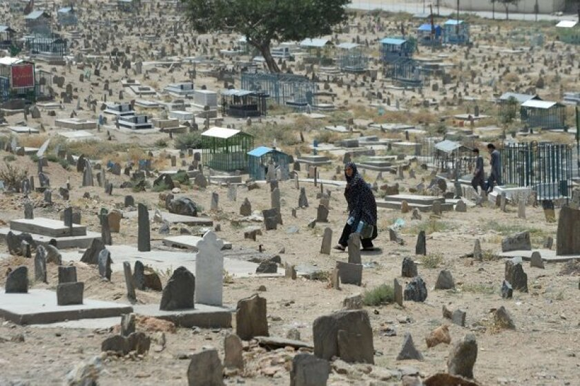 A woman walks in a cemetery in Kabul, Afghanistan. Civilian casualties in the Afghan war rose 23% in the first half of this year, the United Nations reported.