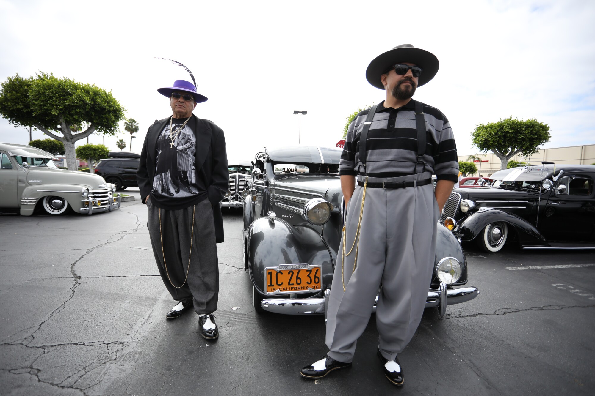 Two men in pants pegged at the ankle, with long chains, hats and shining saddle shoes, stand near classic cars.