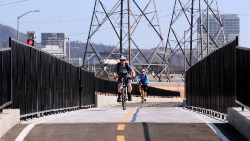 Cyclists pass over a newly constructed pedestrian and bicycle bridge over a culvert near Flower Street and Fairmont Avenue on a recent Saturday. The bridge is part of the second phase of the Glendale Narrows Riverwalk project.