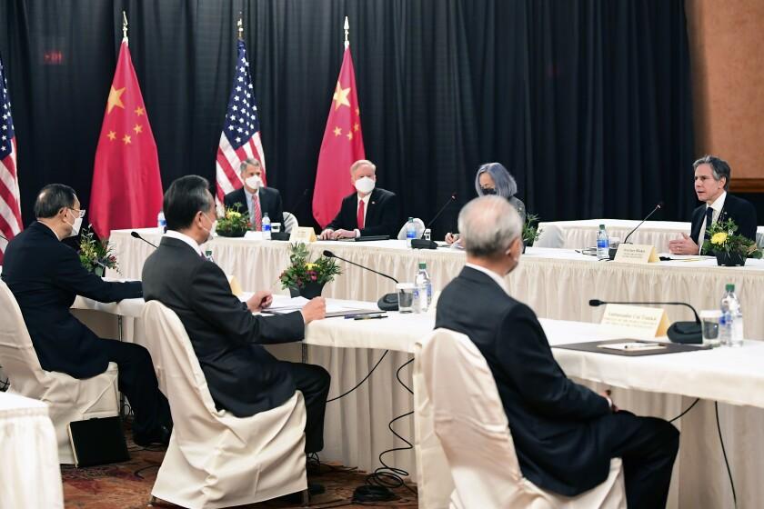 Secretary of State Antony Blinken speaks across a table to Chinese officials.
