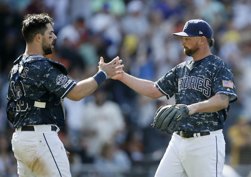 San Diego Padres catcher Austin Hedges congratulates relief pitcher Kirby Yates after they defeated the San Francisco Giants on March 31, 2019.