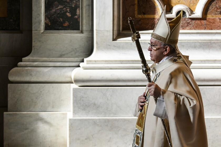 Pope Francis, in robes and mitre, walks by marble columns in the Vatican.