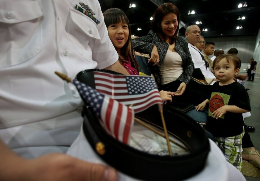 An immigrant from the Philippines waits with her children before the start of a naturalization ceremony in Los Angeles last year.