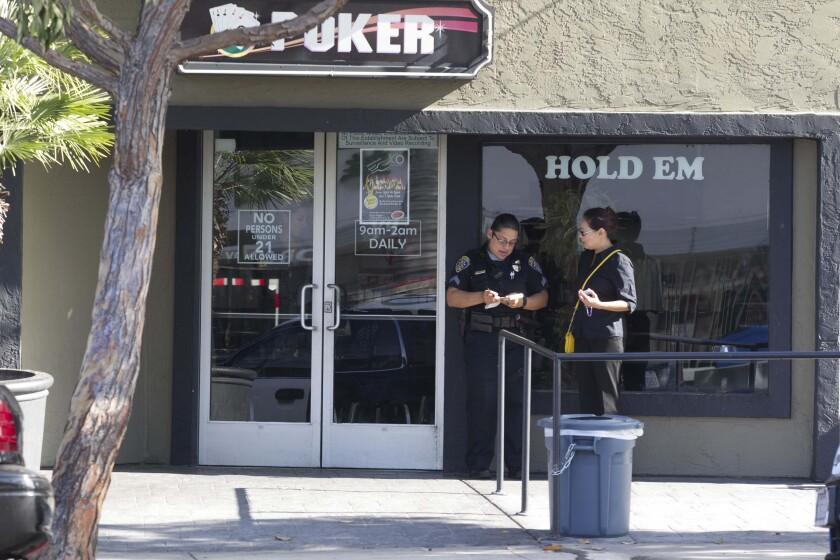 Un agente de policía habla con un empleado del Lucky Lady Card Room and Casino durante un cateo realizado en julio de 2016
