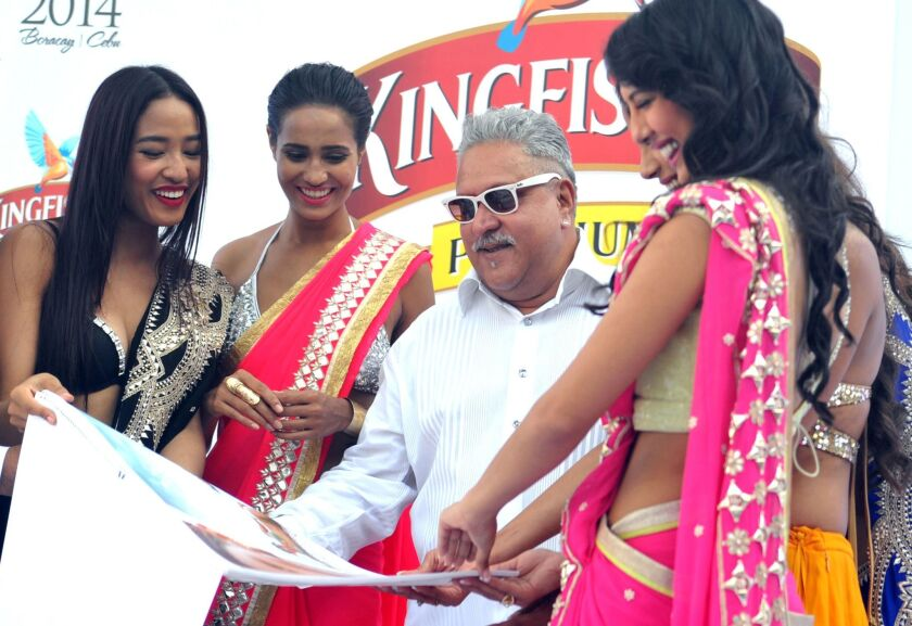 The Indian liquor baron Vijay Mallya is shown in December 2013 with models during the launch of the Kingfisher 2014 calendar in Mumbai, India.