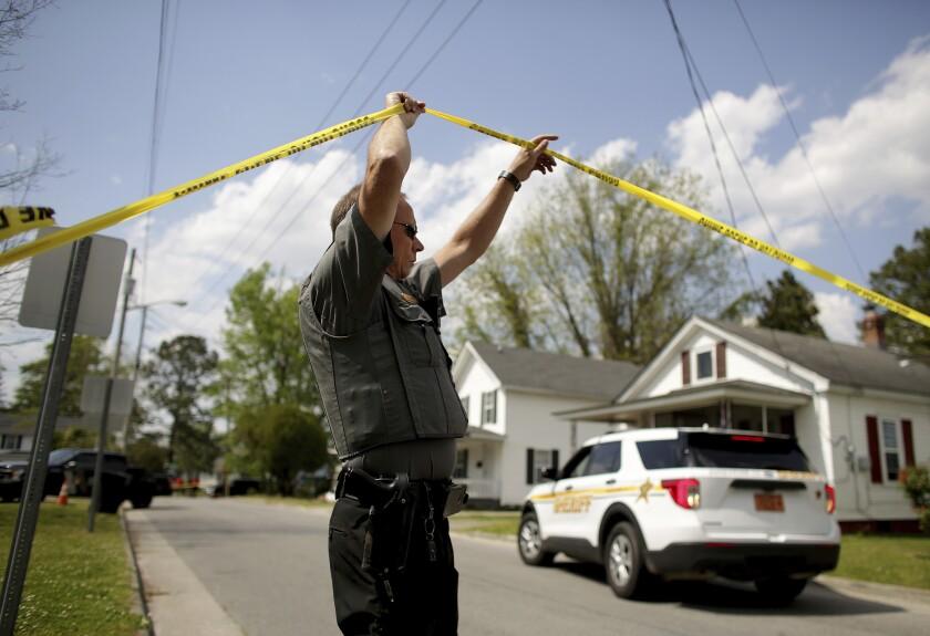 A uniformed man walks under yellow police tape on a neighborhood street.