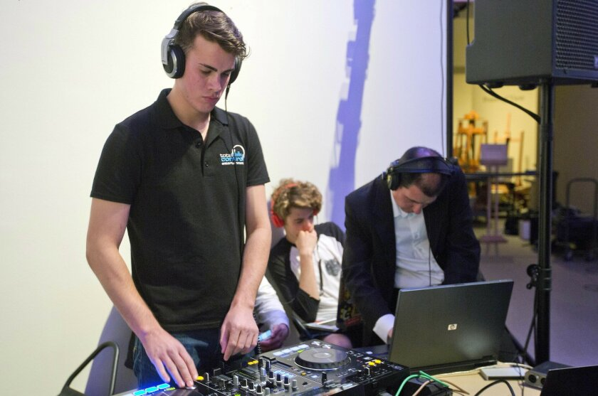 In this Wednesday, May 18, 2016, photo, Dartmouth College undergraduate Christopher Hogan, left, spins a 10-minute set of music during a competition on campus in Hanover, N.H., where dancers were asked to determine whether the music was generated by humans or a computer algorithm. (AP Photo/Michael Casey)