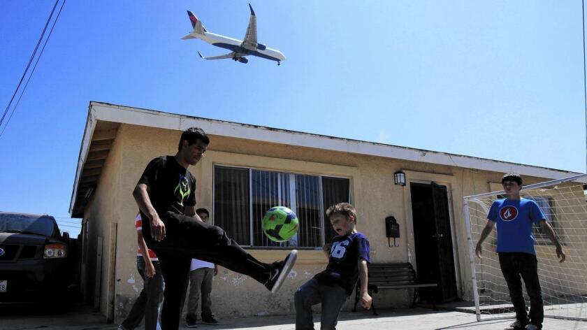 Niños juegan futbol afuera de su casa ubicada en Lennox, una comunidad donde el 99% de sus residentes son inmigrantes latinos. Esta zona está a unas millas del aeropuerto, ruta directa de algunas líneas aéreas.
