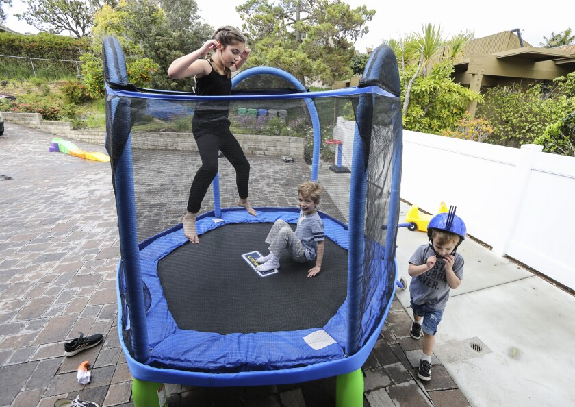 The Daniels children (from left) Ashlan, 9, Cole, 6, and Grant, 2, of El Cajon, play in the front yard of their Fletcher Hills home on Thursday with new toys purchased since they have had to stay at home because of COVID-19.