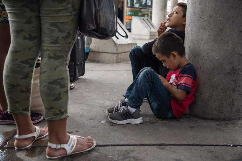 Central American migrant families recently released from federal detention wait to board a bus at a bus depot in McAllen, Texas, this month.