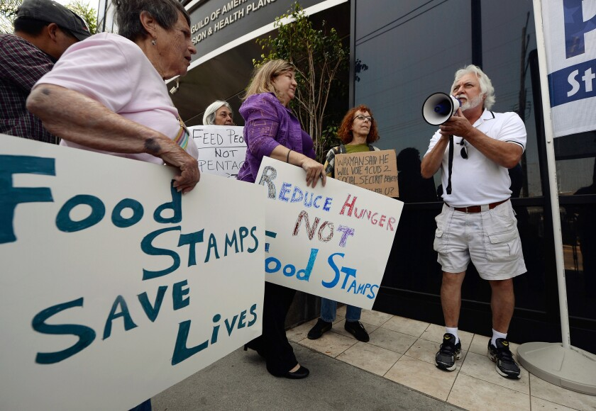 The House farm bill threatens $20.5 billion in cuts over a decade to food stamps. Above: Tom Camarello with Progressive Democrats of America and members from several other organizations hold a rally in front of Rep. Henry Waxman's office in Los Angeles.