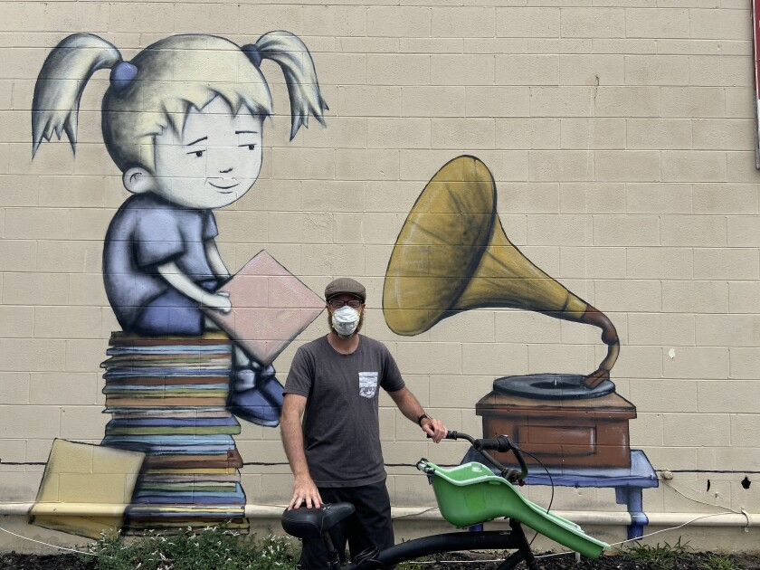 "Carlsbad-based artist Bryan Snyder with his mural ""Introducing Jingle"" on an outside wall of Carlsbad Village Music."